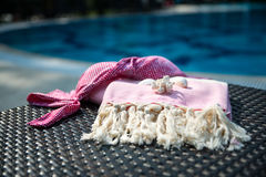 Close-up of a white and pink Turkish peshtemal / towel, pink bikini top and white seashells on rattan lounger. Stock Photo
