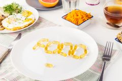 Close up white plate with Food word lettering by vitamin pills on the served wooden table with breakfast meal. Pill instead of foo royalty free stock photo