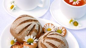 A close-up, a white plate with pastries, biscuits and cookies, decorated with white daisies. On white saucers there are. Two white cups with chamomile tea stock video