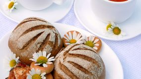 A close-up, a white plate with pastries, biscuits and cookies, decorated with white daisies. On white saucers there are stock footage