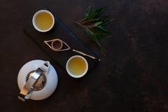 Close up of White porcelain Asian tea set with green Japan Matcha tea on black stone desk.  stock image