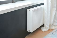 White radiator heating with thermostat for energy saving. Close up on White radiator heating with thermostat for energy saving Royalty Free Stock Photo