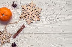 Close up. White rustic table with tangerines, cinnamon, anise-star, wooden snowflakes, artificial snow. Copy space stock images