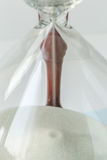 Close up white sand flowing of vintage wooden hourglass on white Royalty Free Stock Photos
