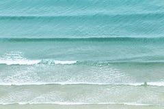 Close up white soft wave rolling splash on empty tropical sandy beach stock photos