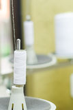 Close up of white spool of thread conected to a sewing machine Royalty Free Stock Photos