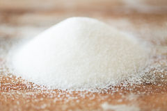 Close up of white sugar heap on wooden table Royalty Free Stock Photo