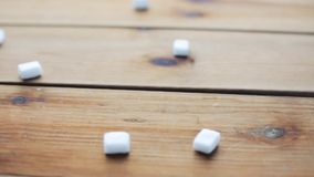 Close up of white sugar on wooden board or table. Food, junk-food, carbohydrates, cooking and unhealthy eating concept - close up of white lump sugar on wooden stock video