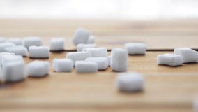 Close up of white sugar on wooden board or table. Food, junk-food, carbohydrates, cooking and unhealthy eating concept - close up of white lump sugar on wooden stock video footage