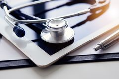 White tablet and stethoscope on table. Medical equipment on table stock images