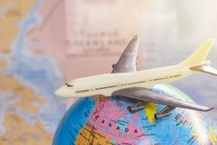 Close up the white toy airplane on the mimicry and blurred world. Map background. Travel and business concept Royalty Free Stock Photos