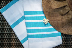 Close-up of white and turquoise color Turkish peshtemal / towel, white seashells and straw hat on rattan lounger. Royalty Free Stock Photos