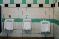 Close up white urinals men public toilet in ceramic urinals in toilet room. Close up white urinals men public toilet in ceramic urinals for men in toilet room royalty free stock photo
