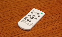 Close up of white video bim remote control on the wooden table. Close up of white video bim remote control on the wooden table royalty free stock image
