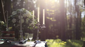 Close up of white vintage candelabrum on the wedding decorated table in the forest. Bouquet of white roses on background. Romantic dinner in the forest stock video footage
