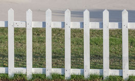 Close up the white wooden fence nearby pathway and green grass. Stock Images