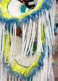 Close Up of a White, Blue and Yellow Headdress and Bustle at a Pow Wow. Close up of a white, yellow and blue headdress and bustle worn by a male fancy dancer at royalty free stock photos