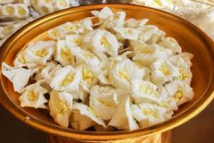 Closeup of white and yellow Sandalwood flowers or artificial fl. Close up of white and yellow Sandalwood flowers or artificial flowers on the golden tray with Royalty Free Stock Photos