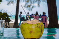 Close-up of whole coconut fruit with drinking straw on a plastic table by the beach Royalty Free Stock Photography