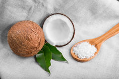 A close-up of whole and cut coconuts with leaves and a wooden spoon with coconut chips on a fabric. Two coconuts and nut flakes Royalty Free Stock Photo