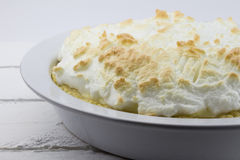 Close up of whole uncut lemon meringue pie on white rustic wood Royalty Free Stock Image