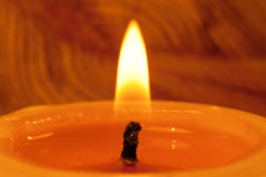 Close-up of  wick and flame of burning candle on light backgroun Stock Image