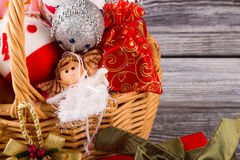 Close-up of a wicker basket with Christmas decor. Little fairy, balls and gifts. New Year decoration Stock Photos