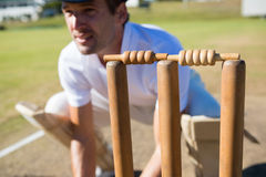 Close up of wicket keeper crouching by stumps. During match on sunny day royalty free stock photography