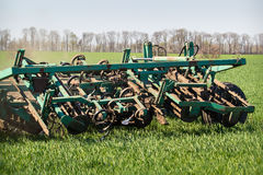 Close-up wieden-machine achter tractor op groen tarwegebied Royalty-vrije Stock Afbeeldingen