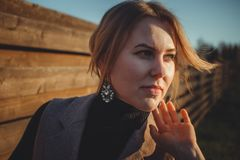Close up. Wind develops hair stylish girl with beautiful jewelry. Portrait of a woman in brown tones.  royalty free stock images