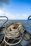 Close-up windings of rope at the head of the boat, on the sea. Blue sky with clouds, Vietnam Stock Photo