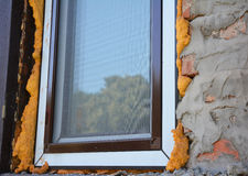 Close up on window insulation with foam. Windows installation. Royalty Free Stock Photo