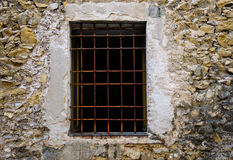 Close up Window with iron bar grill. In stone wall Royalty Free Stock Images