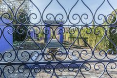 Close up of a window with a metal bars and in the background you can see a fountain a purple arch and green vegetation royalty free stock photography