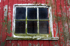 Close up of window on old red barn in Illinois. An old red barn window with peeling paint and moss growing Royalty Free Stock Photography