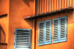 Close up of windows in an orange wall in Florence Stock Photos