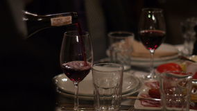 Close up of wine poured in glass isolated on a dinner table stock video