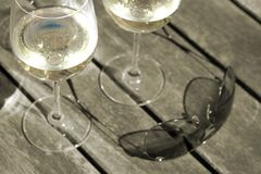 Close-up of wine & sunglasses on patio table - ton Stock Photography