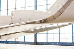 Close up wing detail on an executive jet. Close up wing and engine detail on an executive corporate jet parked in a hangar at an airport in an aviation, travel Stock Image