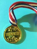 Close-up of winnier golden medal. Close-up of golden shinning winning medal with colorful ribbon stock images