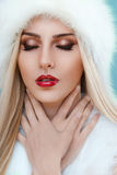 Close up of winter lady with strong red lipstick. Young beautiful woman's face with luxury makeup . Blonde lady with red lipstick and close eyes. Far fashion Royalty Free Stock Images