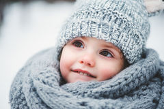 Close up winter portrait of adorable smiling baby girl. In grey knitted hat and scarf Stock Image