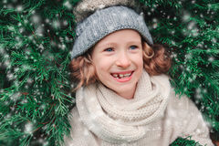 Close up winter portrait of happy child girl wearing warm knitted hat and scarf with Christmas tree Royalty Free Stock Photo