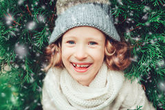 Close up winter portrait of happy child girl wearing warm knitted hat and scarf with Christmas tree Stock Images