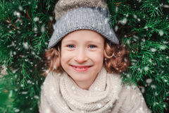 Close up winter portrait of happy child girl wearing warm knitted hat and scarf with Christmas tree Royalty Free Stock Image