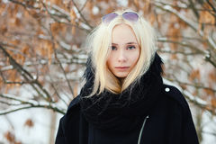 Close up winter portrait: young blonde woman dressed in a warm woolen jacket posing outside in a snowy city park with foliage back stock images