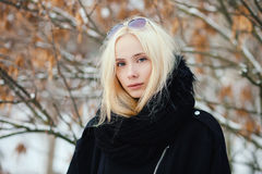 Close up winter portrait: young blonde woman dressed in a warm woolen jacket posing outside in a snowy city park with foliage back Stock Photos
