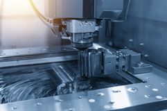 Close-up of the wire - EDM CNC machine while cutting the sample. Work pieces in light blue tone and lighting effect Royalty Free Stock Photos