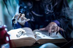 Wicth`s Hand On Magic Book. Close up of a witch`s hands with pointed black nails holding bones above book of a magic recipe Royalty Free Stock Photo