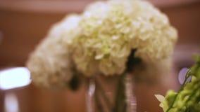 Close-up witte bloemen voorraad Vakantiebloemen in vaas Bloemdecoratie op de huwelijkslijsten stock videobeelden